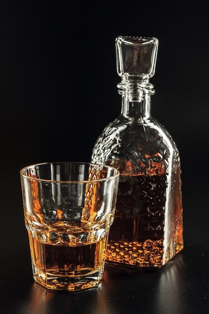 Glass of the whiskey and a square decanter Premium Photo