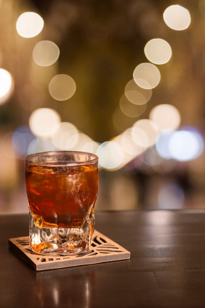 Glass of whiskey with bokeh effect Free Photo