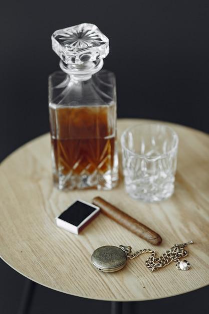 Bicchiere di whisky con sigaro sul tavolo. close up foto di alcol e sigari. Foto Gratuite
