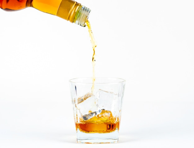 The glass of whiskey with cool ice on the white background Premium Photo