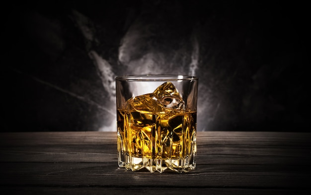 Glass of whiskey with ice on black background Premium Photo