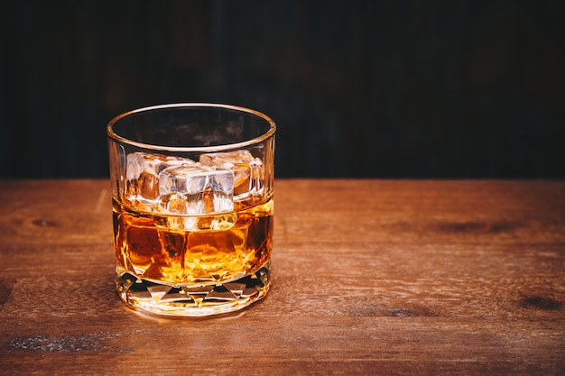 Glass of whiskey with ice cube on wooden table over black background Premium Photo