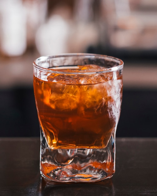 Glass of whiskey with ice cube Free Photo