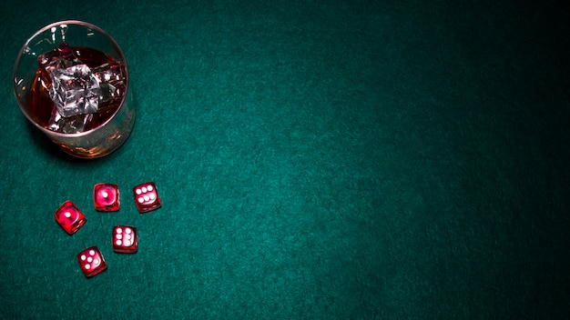 Glass of whiskey with ice cubes and red dices on green poker background Free Photo
