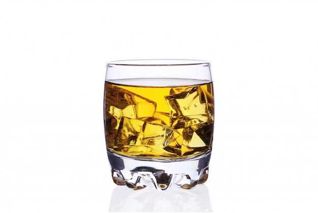 A glass of whiskey with ice cubes on a white background isolate. Premium Photo