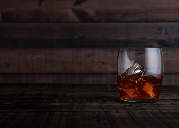 Glass of whiskey with ice cubes on wooden table background Premium Photo