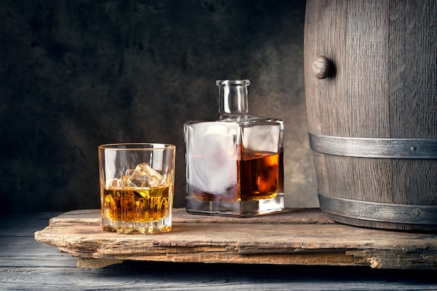 Glass of whiskey with ice decanter and barrel Premium Photo