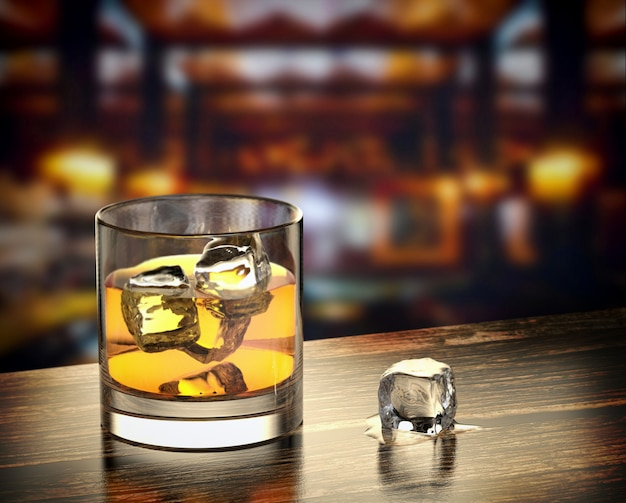 Glass of whiskey with ice on the wooden table with a blurred bar background. Premium Photo