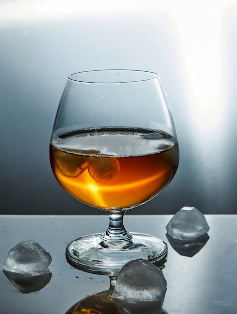 A glass of whiskey with ice. Premium Photo
