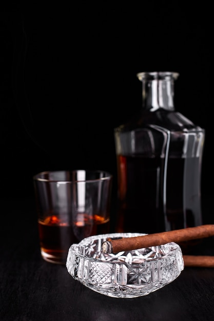 Glass of whiskey with smoking cigar. whisky, tobacco Premium Photo