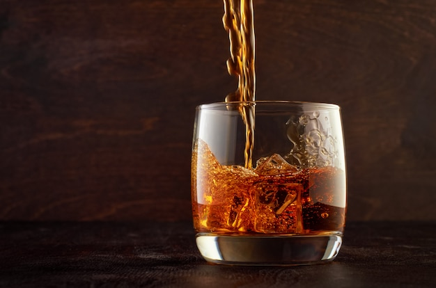 Glass of whiskey on a wooden table Premium Photo