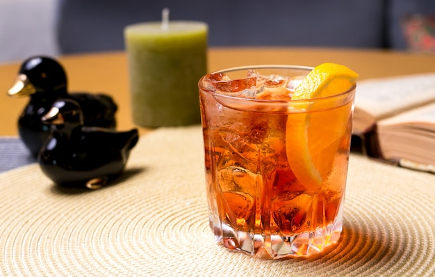 A glass of whisky on the table with sliced lemon and ice side view Free Photo