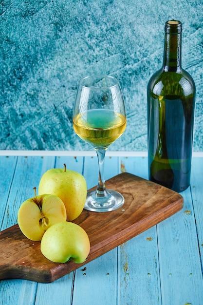 Un bicchiere di vino bianco e una bottiglia con fette di mela sulla parete blu. Foto Gratuite