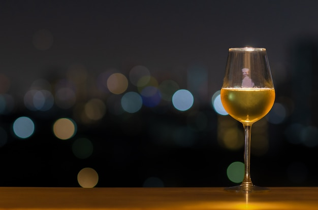 A glass of white wine on wooden table of rooftop bar with colorful bokeh of city light and copyspace Premium Photo