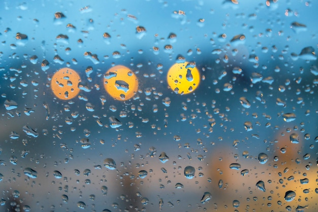 Glass window covered in raindrops with lights on the blurry background Free Photo
