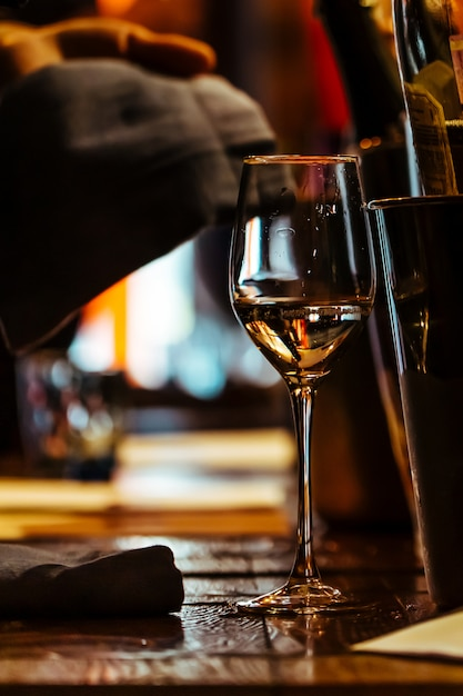 A glass of wine on the wooden table of the restaurant. Premium Photo