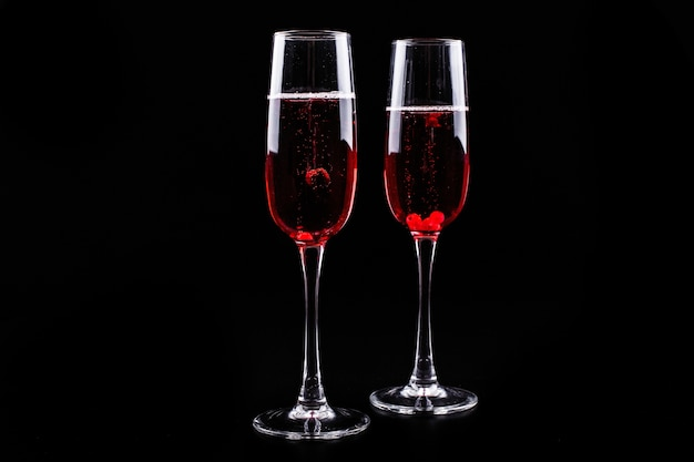 Glass with berries and red champagne alcohol cocktail stands on black background Free Photo