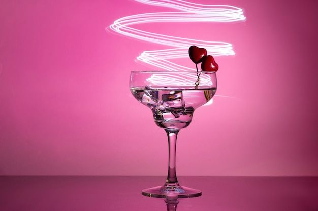 Glass with a cocktail and two hearts. valentine's day and wedding concept. Premium Photo