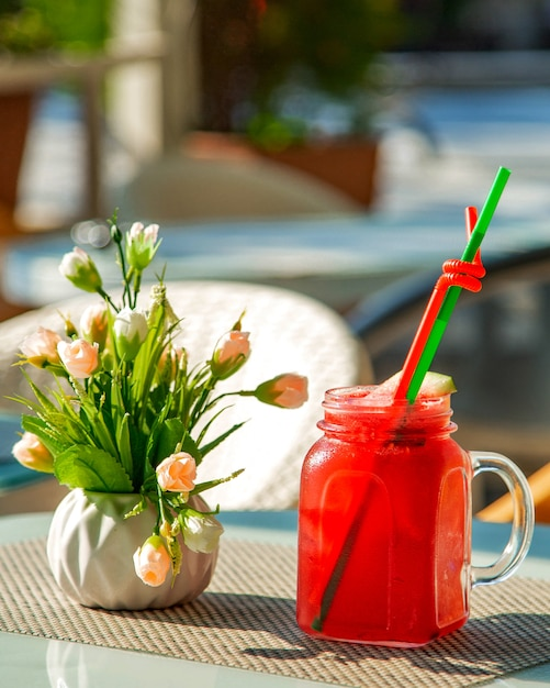 Glass with cold watermelon juice and a vase of flowers Free Photo