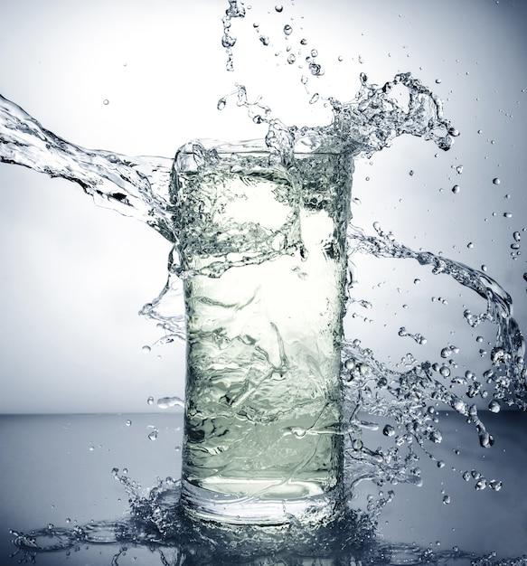 Glass with ice and liquid splash Premium Photo