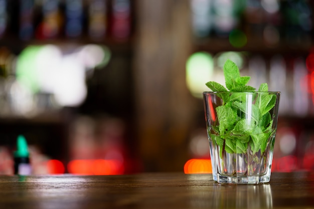 A glass with mint stands on wooden rack in the bar Premium Photo