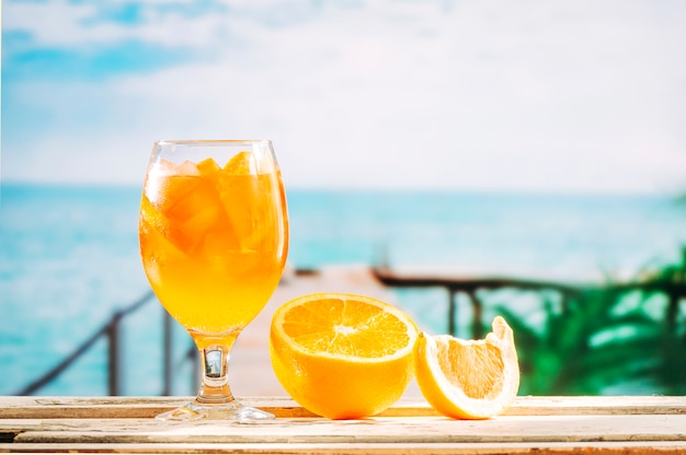 Glass with orange drink and sliced orange on wooden table Free Photo