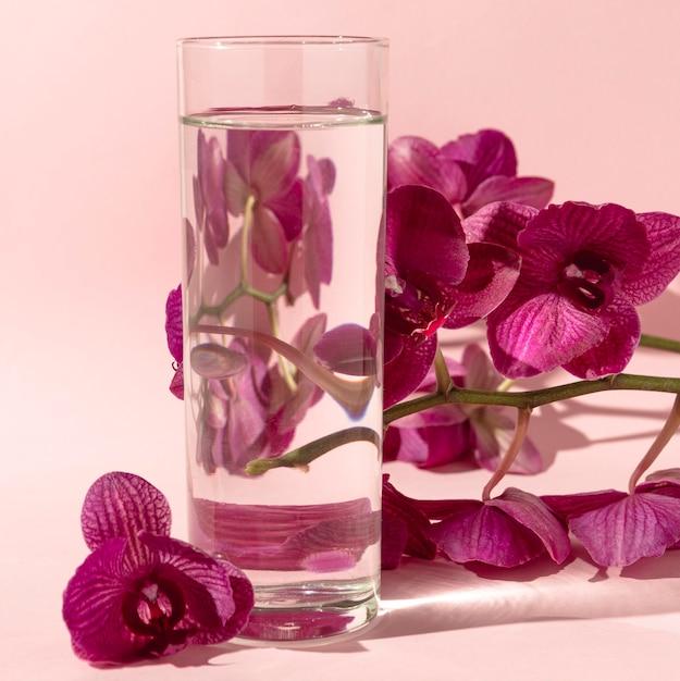 Bicchiere con acqua accanto ai fiori Foto Gratuite