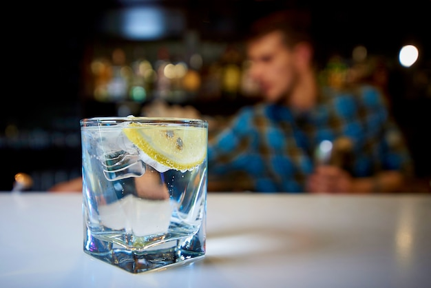 A glass with water, lemon and ice on the bar. Premium Photo