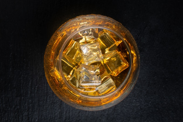 Glass with whiskey and ice on black table. top view. Premium Photo