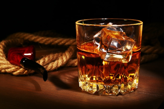 Glass with whiskey, ice cubes and smoking pipe. Premium Photo