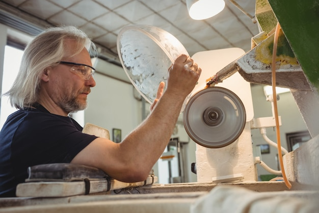 Glassblower polishing and grinding a glassware Free Photo
