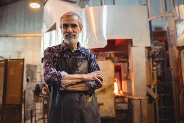 Glassblower standing with arms crossed at glassblowing factory Free Photo