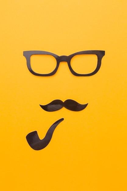 メガネと黄色の背景上のパイプ 無料写真