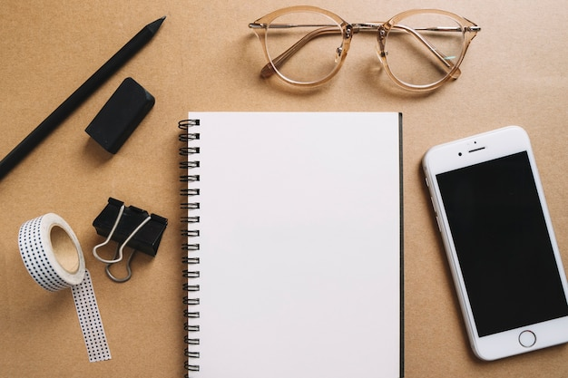 Glasses and smartphone near office supplies Free Photo