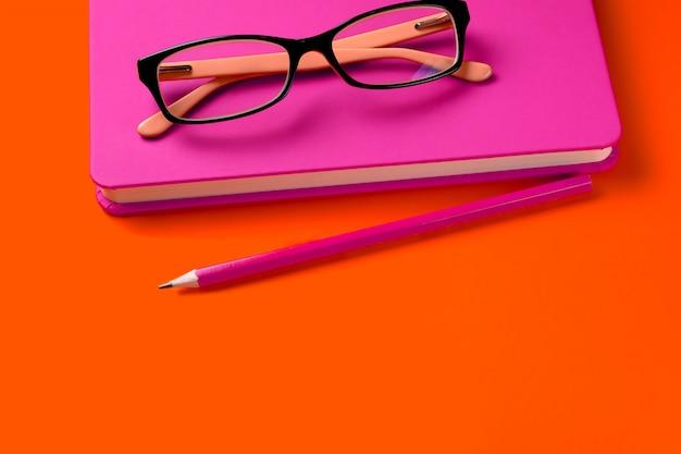 The glasses are lying on a pink notebook, next to a pencil, against a background of lush lava. workplace freelancer, businessman, entrepreneur. Premium Photo