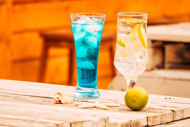 Glasses of blue mint drinks and lime with starfish at wooden table Free Photo