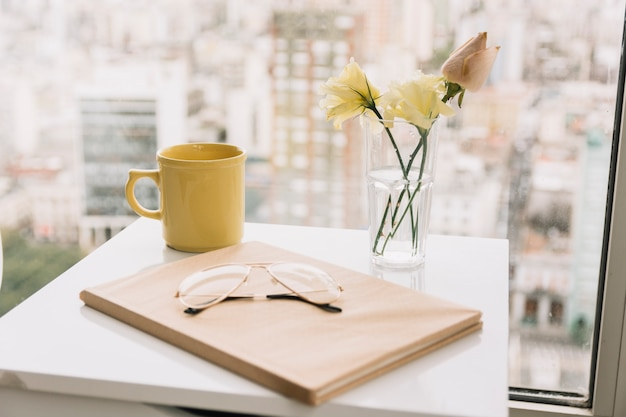Glasses and book near flowers and mug on table Free Photo