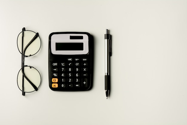 Glasses, calculator and pen. office supplies and education concept. Premium Photo