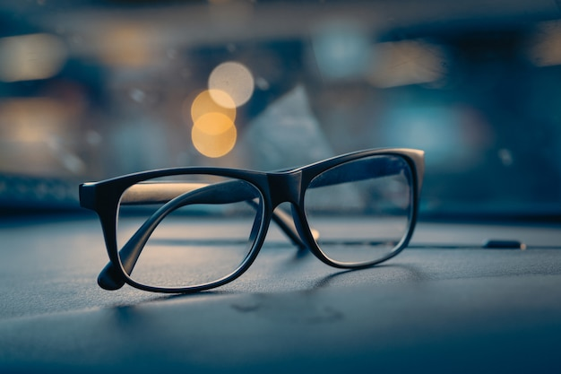 Glasses on car console with city light Premium Photo