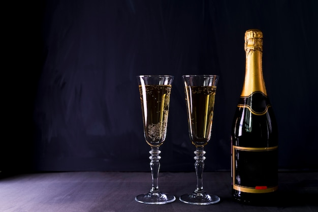 Glasses of champagne with bottle on table Free Photo