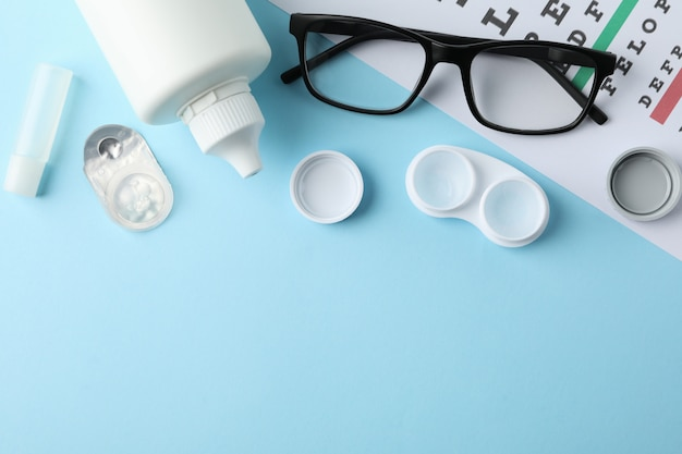 Glasses, contact lenses and eye test chart on blue surface, top view Premium Photo