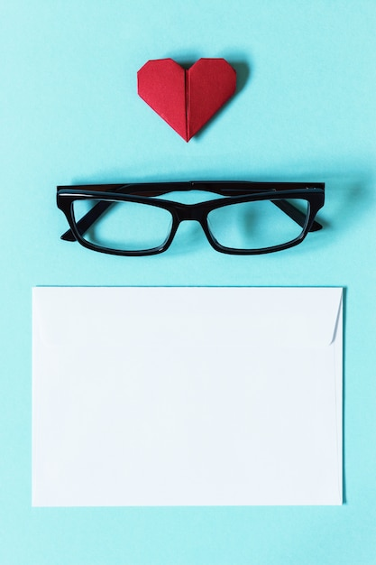 Glasses in dark frame, white blank envelope and red heart of origami Premium Photo