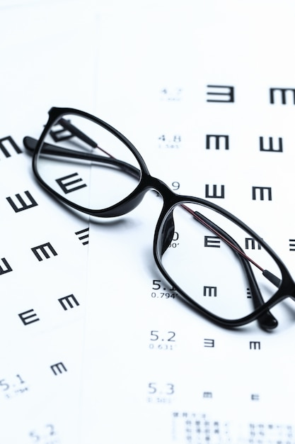Glasses and eye chart on white background Photo | Free Download