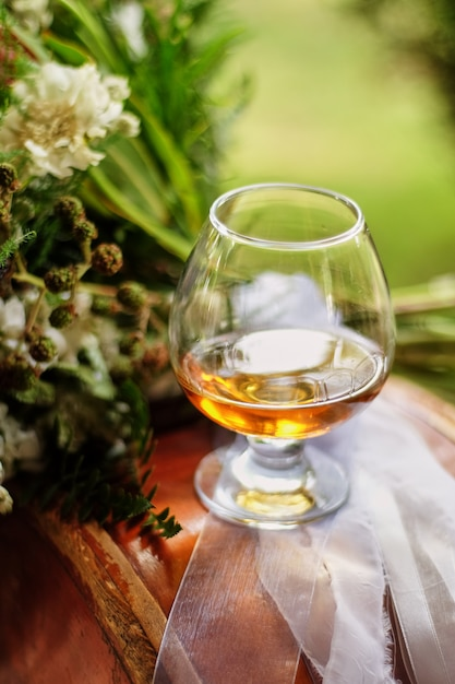 Glasses filled with brandy, one glass on the table next to the flower Premium Photo
