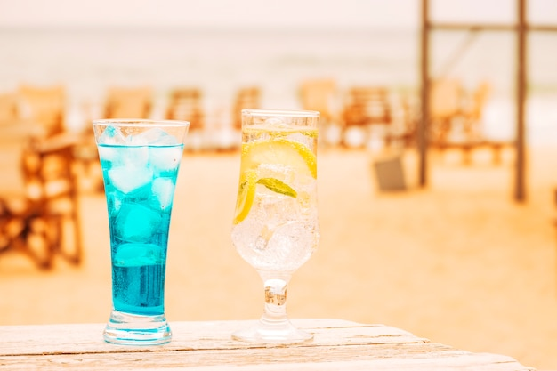 Glasses of fresh blue mint drinks at wooden table Free Photo