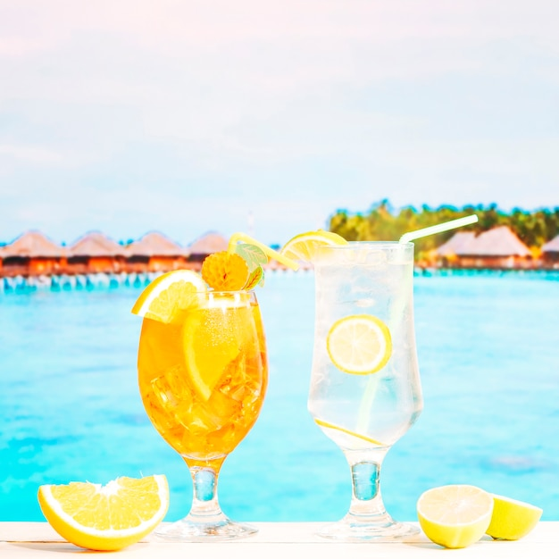 Glasses of juicy lemon orange drinks with straw and sliced citruses Free Photo