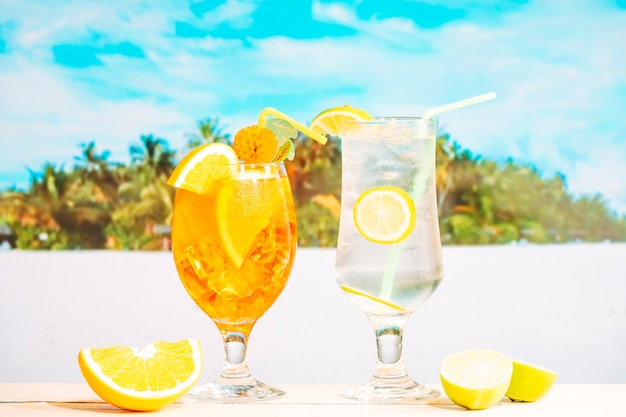 Glasses of juicy orange lemon drinks with straw and sliced citruses Free Photo