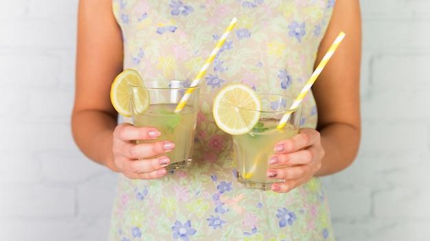 Bicchieri di limonata tenuti da una donna Foto Gratuite