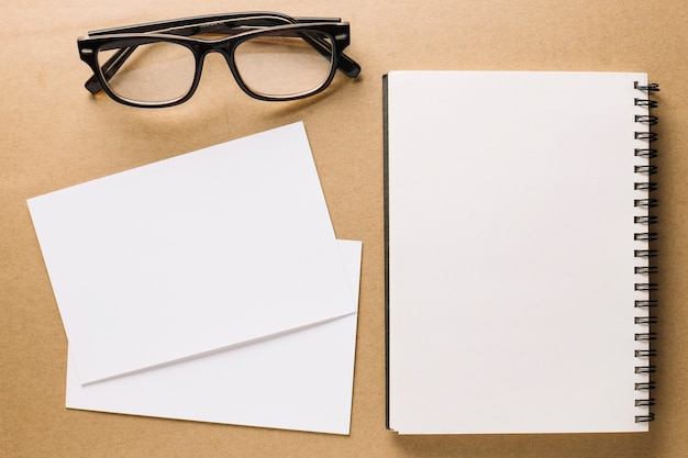 Glasses near notebook and paper sheets Free Photo