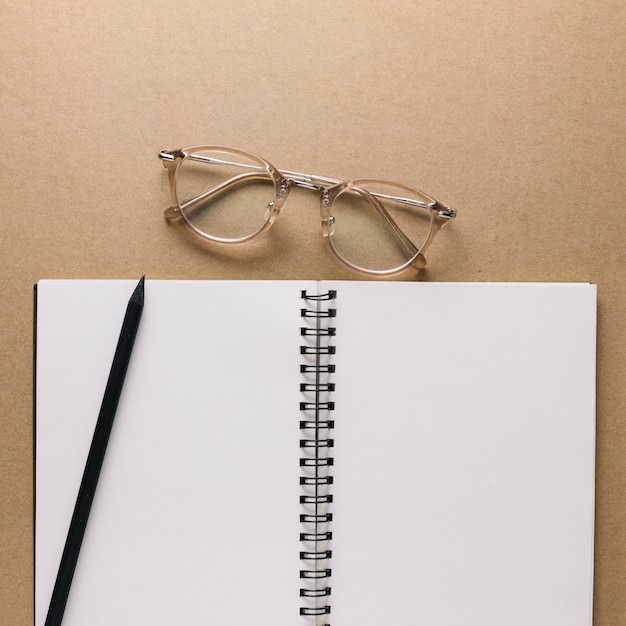 Glasses near notebook and pencil Free Photo